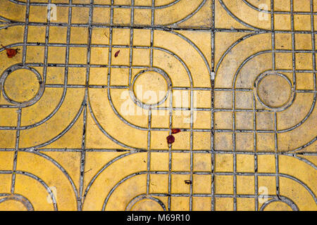 yellow patterned paving tiles on the street, top view. Cement bricks, squared stone ground floor background texture. - Stock Photo