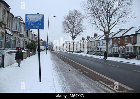 London, UK. 1st Mar, 2018. Romford Road partly covered with snow after  heavy overnight snowfall as Storm Emma and - Stock Photo