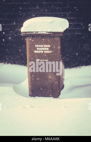 Snow Lying On A Recycling Wheelie Bin (Trash Can) In The UK During A Snow Storm With Copy Space - Stock Photo