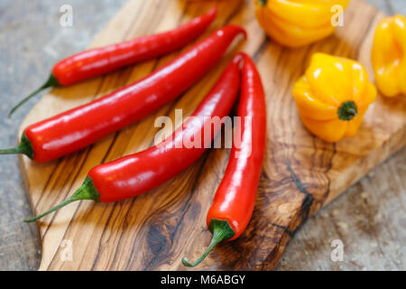 Close up of red and yellow hot peppers on cutting board on old wooden table - Stock Photo