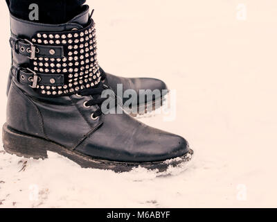 female black boots on snow - Stock Photo