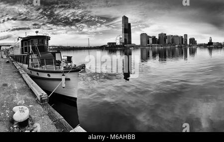 Moody charming panorama of Melbourne Docklands area with docked historic wooden boat and distant modern urban towers - Stock Photo