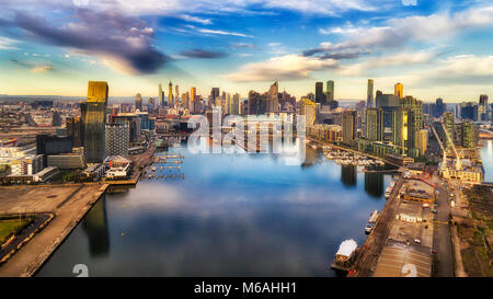 Yarra river surrounded by Melbourne suburb Docklands in elevated aerial view facing city CBD waterfront and towers - Stock Photo