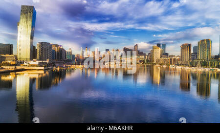 Still Yarra river bay water reflects modern urban architecture of Melbourne Dockalds suburb with bended apartment - Stock Photo