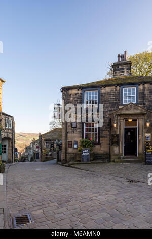 Haworth village where Bronte sisters lived, view down steep, quaint, narrow Main Street, Black Bull pub in foreground - West Yorkshire, England, UK.