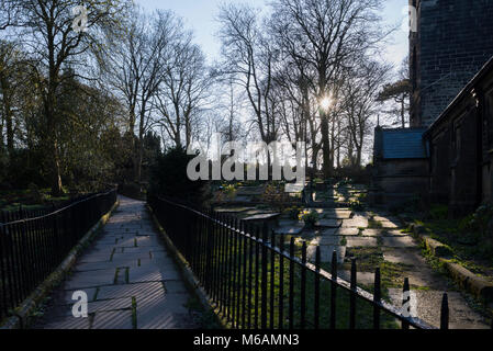 Sunburst through branches casts light over graves by paved path in graveyard - St Michael & All Angels Church, Haworth, - Stock Photo