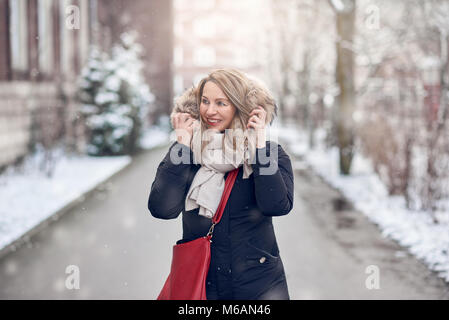 Smiling young woman walking along a snowy road in winter holding the fur trim on her jacket looking to the side - Stock Photo