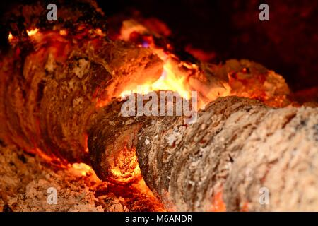 View into a fireplace with close up of a blazing burning logs. - Stock Photo