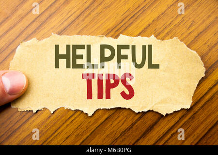 Writing text showing Helpful Tips. Business concept for Help in FAQ or Advice, written on note paper on wooden background - Stock Photo
