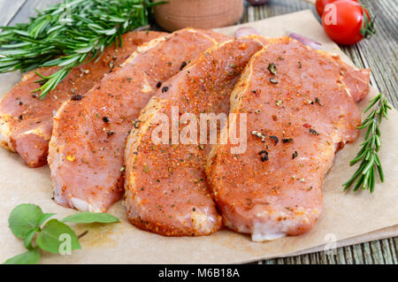 Fresh and raw meat. Sirloin steaks in a row ready to cook. Large pieces of raw meat in marinade with spices on paper - Stock Photo