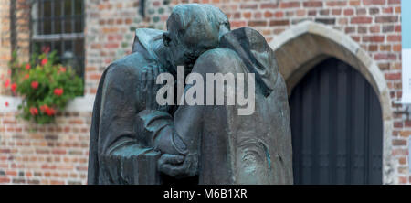Pax, Two monks embrace,one old one young,This statue sculptured by Octave Rotsaert can be found in the courtyard - Stock Photo