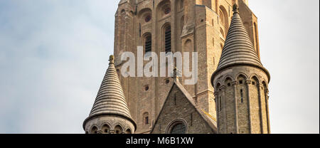 Two conicle brick spires of the Church of Our Lady  foreground the church's magnificent tall tower - Stock Photo
