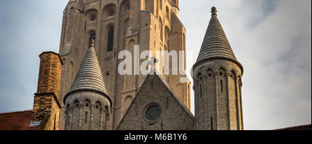 Two conicle spires and an ornate brick chimney of the Church of Our Lady  foreground the church's magnificent tall - Stock Photo