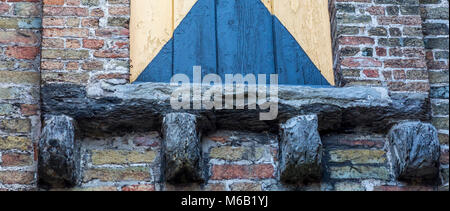 Ornate hand carved stone corbels adding structural support on an ancient medieval building's brick window frame - Stock Photo