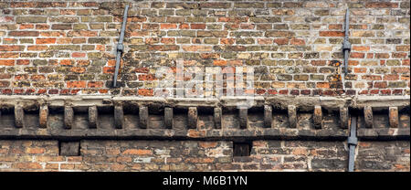 Ornate stone corbels adding structural support on an ancient medieval building's brick side elevation on the canal - Stock Photo