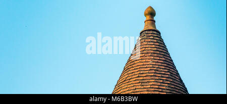 Conical clay tiled spired roof of the Church of our Lady in the Medieval City of Bruges against a blue October sky - Stock Photo