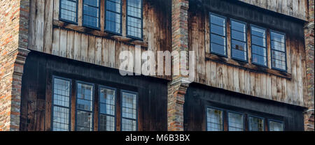 Weathered wooden leaded glass windows on a wooden fronted house in Bruges which overlooks the canal's waterway - Stock Photo
