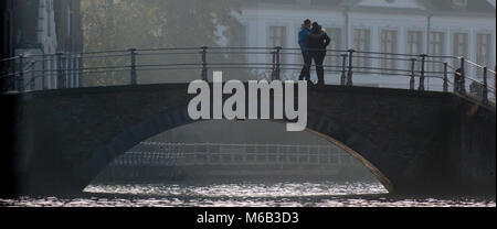 Couple silhouetted on a Bruges bridge on the canal - Stock Photo