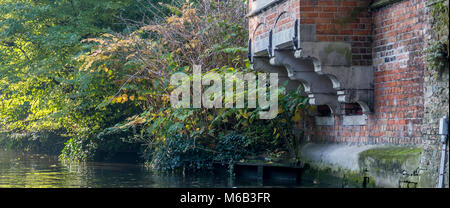 Ornate stone hand carved corbels supporting a brick bay on the canal in Bruges - Stock Photo