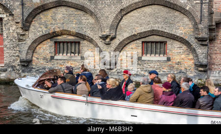 Tour boat full of tourists on the canal in Bruges passing old brick filigree arches. - Stock Photo