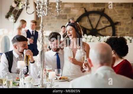 Happy, newly wed couple are socialising with guests at their wedding meal. The bride is sitting on her husband's - Stock Photo