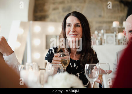 Mother of the bride is raising her glass to a speech toast during the meal at her daughter's wedding. - Stock Photo