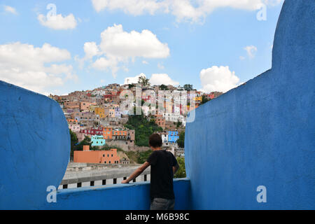 Young man looking over the colorful cityscape of Guanajuato, Mexico, from a blue painted, weirdly shaped balcony. - Stock Photo