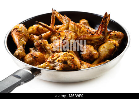Fried chicken drumsticks and wings in frying pan on white background - Stock Photo
