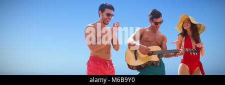 Composite image of friends playing music in swimwear - Stock Photo