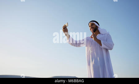 Portrait of Arabian sheikh man with gadget that communicates in  - Stock Photo