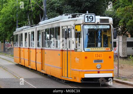 BUDAPEST, HUNGARY - JUNE 20, 2014: People ride orange tram in Budapest. It is part of BKK public transport system - Stock Photo