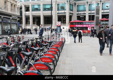 LONDON, UK - APRIL 22, 2016: People walk by Santander Bikes in the City of London. The public bike hire network - Stock Photo