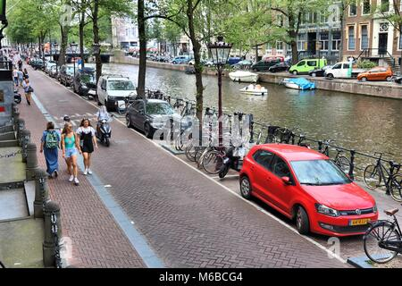 AMSTERDAM, NETHERLANDS - JULY 10, 2017: People visit Herengracht canal in Amsterdam, Netherlands. Amsterdam is the - Stock Photo