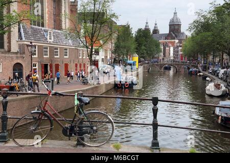 AMSTERDAM, NETHERLANDS - JULY 10, 2017: People visit Oudezijds Voorburgwal in Amsterdam, Netherlands. Amsterdam - Stock Photo