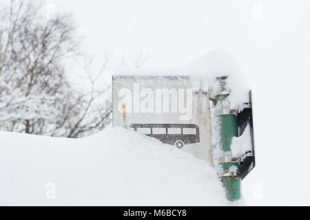 bus stop sign covered in snow - public transport in winter concept - Scotland, UK - Stock Photo
