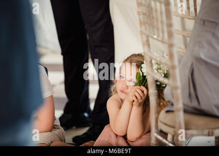 Little girl is sitting on the dancefloor by a table at a wedding. She is watching the bride and groom share their - Stock Photo