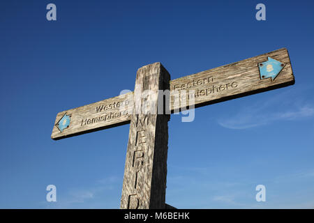A wooden signpost on the South Downs marking the Greenwich Meridian. It points left to the 'Western Hemisphere' - Stock Photo