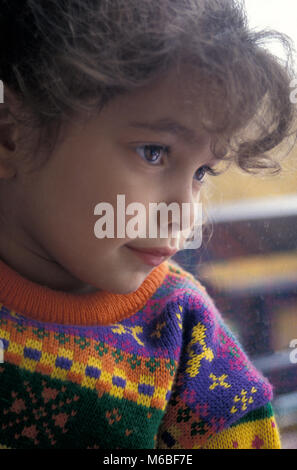 contemplative little girl looking out of window - Stock Photo