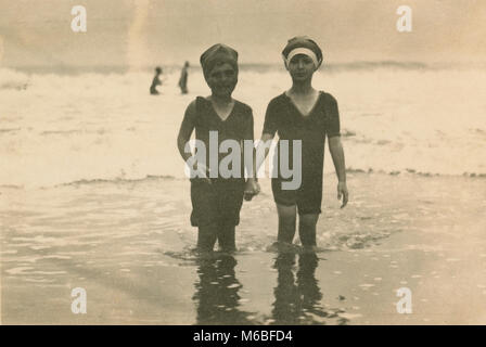 Antique c1900 photograph, two young children in Victorian bathing suits at the ocean. Location unknown, probably - Stock Photo