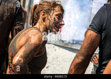 Young woman is smiling after overcoming the last challenge in an open sport challenge; concept of courage, determination - Stock Photo