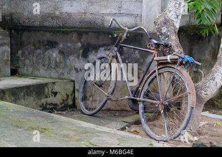 Parked old bicycle near stone wall in Asia. - Stock Photo