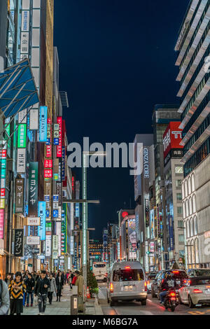 Ginza, Tokyo - December 2017 : Billboards, neon signs and People enjoying nightlife in crowded Chuo dori street - Stock Photo
