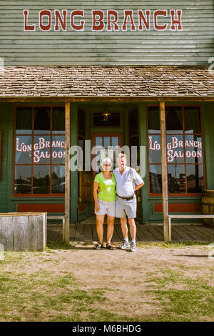 Couple outside Long Branch saloon in Dodge City, Kansas. Building is part of Boot Hill Museum. - Stock Photo