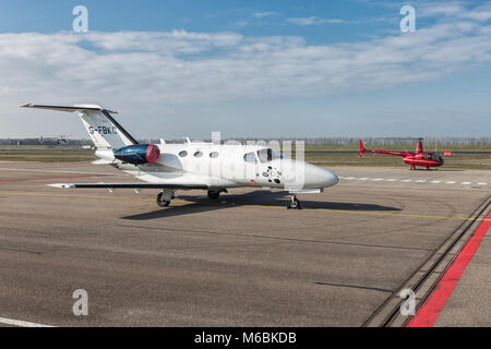 Dutch Lelystad Airport with Cessna jetliner and small helicopter - Stock Photo