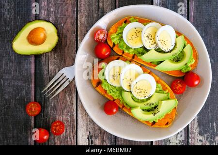 Sweet potato toasts with avocado, eggs and chia seeds on a plate. Top view on a dark wood background. - Stock Photo