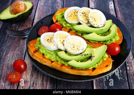Sweet potato toasts with avocado, eggs and chia seeds on a dark plate. Table scene with a wooden background. - Stock Photo