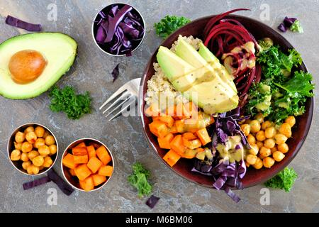 Buddha bowl with quinoa, avocado, chickpeas, vegetables on a dark stone background, Healthy eating concept. Overhead - Stock Photo