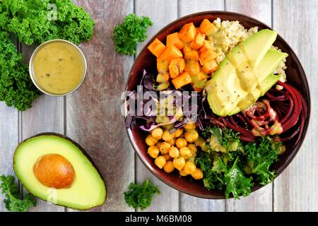 Buddha bowl with quinoa, avocado, chickpeas, vegetables on a wood background, Healthy eating concept. Overhead scene. - Stock Photo