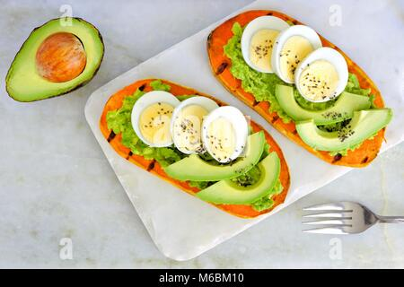 Sweet potato toasts with avocado, eggs and chia seeds on a marble server. Top view on a bright background. - Stock Photo