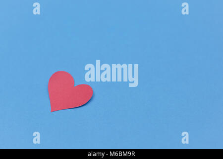 Red paper broken heart on blue background - Stock Photo